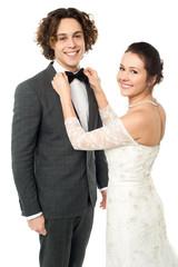 Pretty bride adjusting her man's bowtie