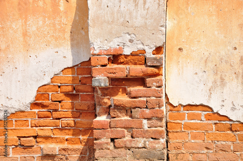 Red clay stained on the white exposed brick concrete wall with p