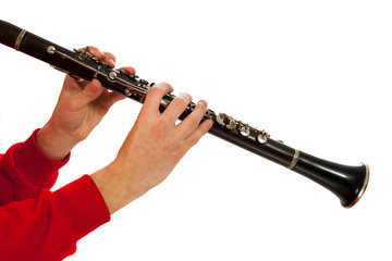 Hands playing on clarinet. Isolated over white background