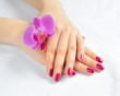 Beautiful hands with manicure and purple orchid flower