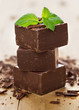 Closeup  pieces of chocolate parts and mint leaves on wooden bac