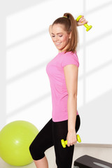 Young beautiful woman exercising with dumbells