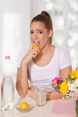 Young beautiful woman licking lemon with grimace on her face