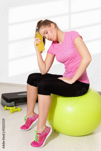 Beautiful young woman resting after tiring workout