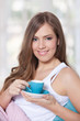 Portrait of a young beautiful woman drinking a cup of coffee