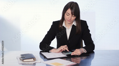 Businesswoman adding bills with calculator.