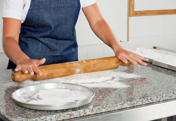 Female Chef Rolling Dough On Counter