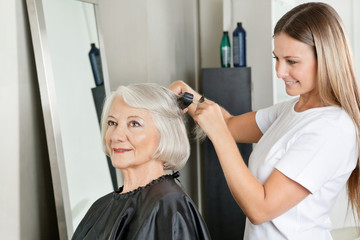 Hairstylist Straightening Woman's Hair At Salon