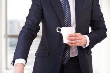 Businessman holding a cup of coffee.