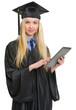 Young woman in graduation gown using tablet pc
