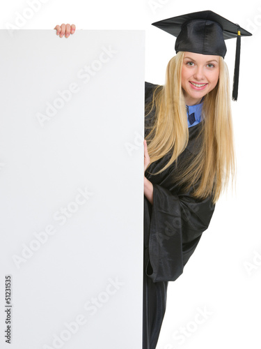 Woman in graduation gown looking out from blank billboard