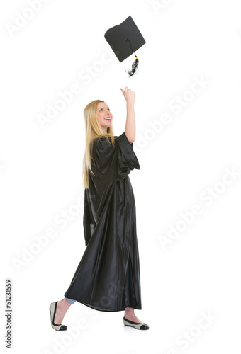 Full length portrait of woman in graduation gown throwing up
