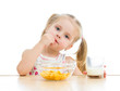 kid girl eating corn flakes with milk over white