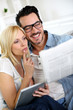 Couple at home reading news