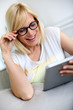 Woman with eyeglasses on using electronic tablet