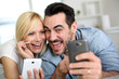 Cheerful couple having fun using smartphone