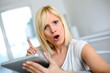 Blond woman using tablet with warning expression