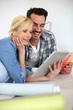 Middle-aged couple choosing wall colours for new home