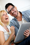 Cheerful couple having fun with digital tablet