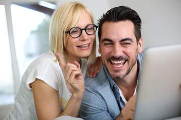 Cheerful couple websurfing on internet with tablet