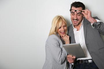Trendy couple websurfing on digital tablet