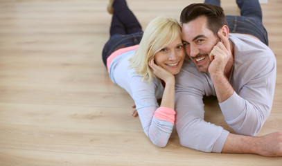 Sweet loving couple laying on wood flooring