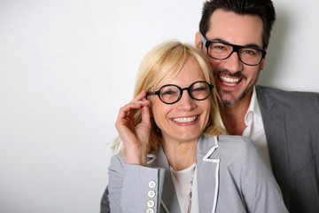 Cheerful couple with eyeglasses on white background