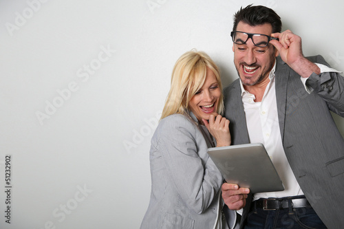 Trendy couple websurfing on digital tablet