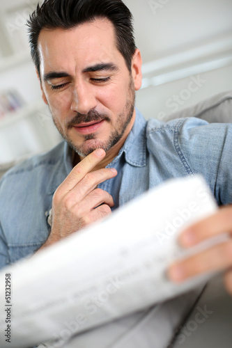 Man reading newspaper with attentive look