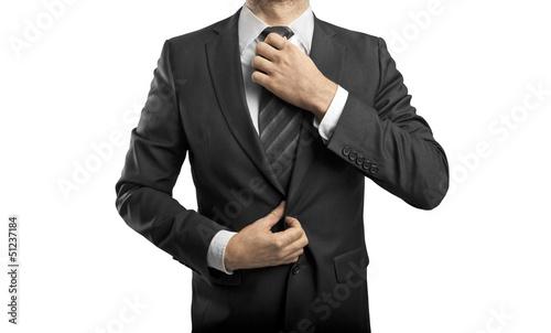 man adjusts tie