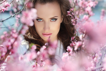 Stare.  Beautiful woman in pink blossoms on spring day