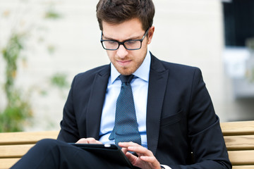 Young businessman using a tablet on a bench in the city