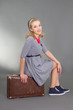 pinup girl sitting on brown retro suitcase
