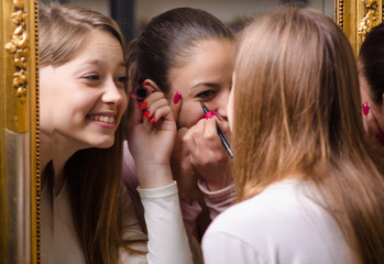 Beautiful teenage girlfriends having fun while putting make up