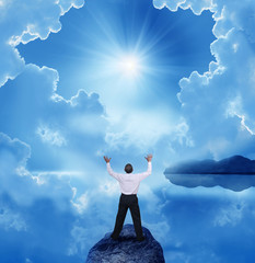 businessman standing with open arms on a rock