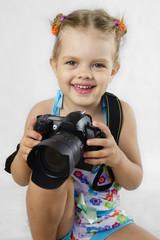 Веселая девочка держит зеркальный фотоаппарат