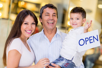 Family holding an open sign