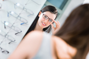 Pretty, young woman choosing new glasses frames