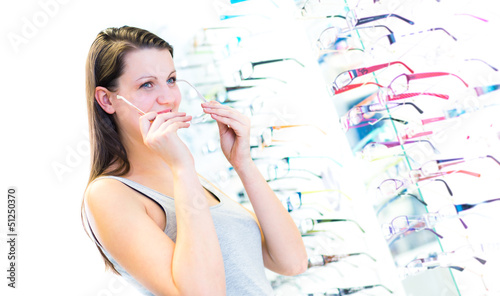 Pretty, young woman choosing new glasses frames in an optician s