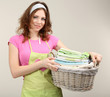 Housewife carrying laundry basket full of clothing