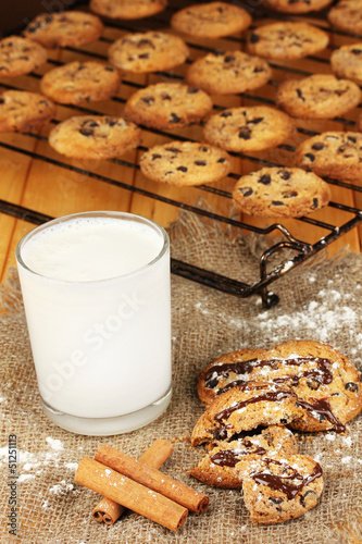 Chocolate cookies on the baking with glass of milk close up