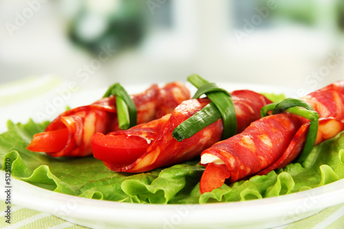 Salami rolls on white plate on bright background