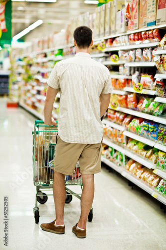 Man in a supermarket running trough the aisle with a shopping ca