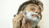 shaving with safety razor and shaving cream over white
