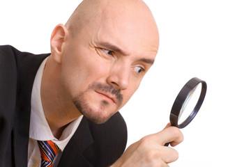 Mann mit Lupe beim genauen prüfen