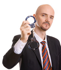 Mann zeigt drohend Handschellen