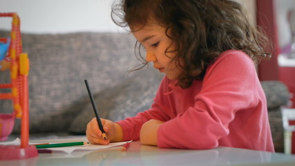 Little girl drawing on piece of paper