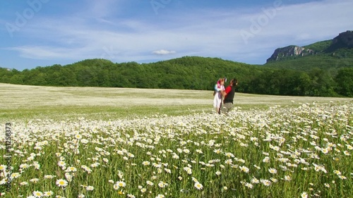 Father and daughter on a walk in a blooming field