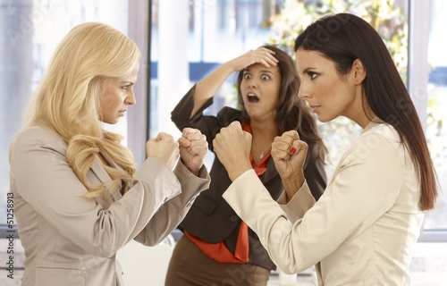 Determined businesswomen fighting at workplace