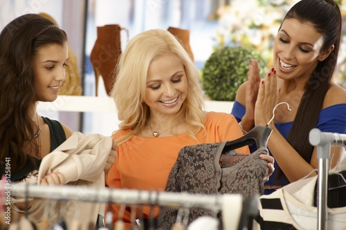Happy females shopping at clothes store